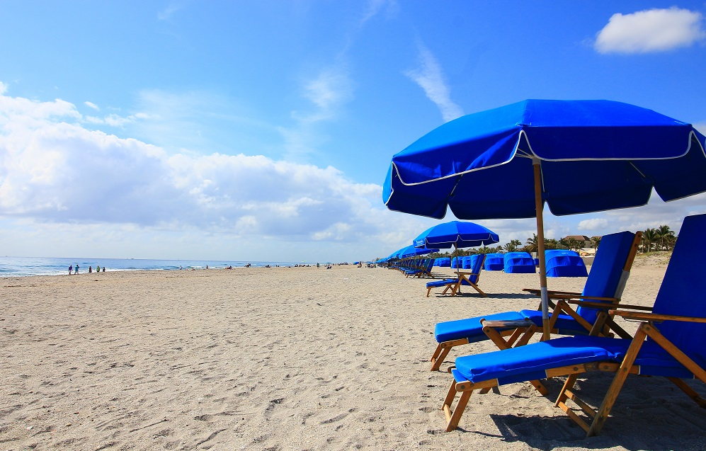 Beach with Blue Umbrellas and Lounge Chairs