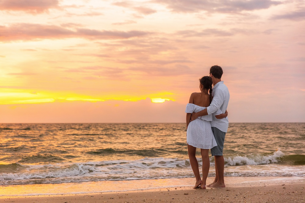 Couple Standing on Beach and Watching the Sunset